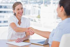 Smiling interviewer shaking hand of an applicant - stock photo