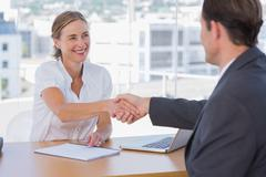 Cheerful interviewer shaking hand of an interviewee - stock photo