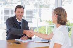 Smiling businessman shaking hand of a job applicant - stock photo