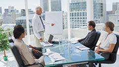 Manager pointing at a chart during a meeting - stock photo