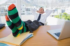 Stock Photo of Business having a nap with feet on his desk