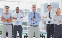 Team of business people standing with arms folded - stock photo
