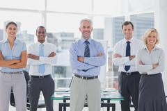 Stock Photo of Team of smiling business people standing with arms folded