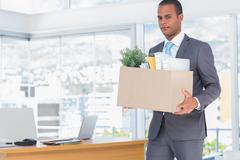 Sad businessman leaving his company - stock photo