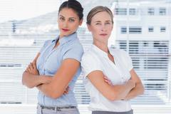Stern businesswomen standing back to back Stock Photos
