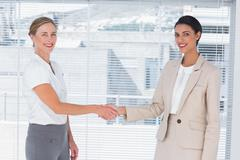 Stock Photo of Two cheerful partners shaking hands