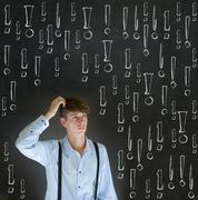 thinking business man with chalk exclamation marks - stock photo