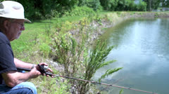 Man thinks he has a bite on fishing line Stock Footage
