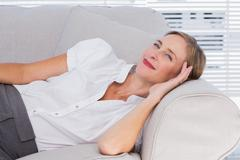 Smiling businesswoman lying on couch - stock photo