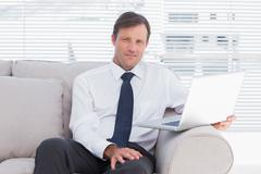 Stock Photo of Businessman sitting on couch looking at camera