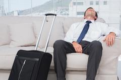 Businessman napping on couch - stock photo