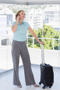 Smiling businesswoman on the phone leaning on suitcase - stock photo