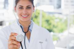 Pretty young doctor holding up stethoscope - stock photo