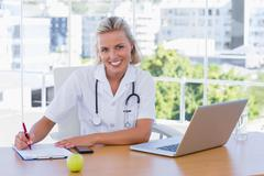 Stock Photo of Beautiful nurse writing on a notepad on her desk