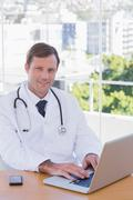 Smiling doctor working on his laptop - stock photo