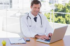 Smiling doctor working on a laptop - stock photo