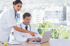 Doctor pointing at the laptop of a colleague Stock Photos