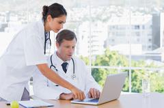 Group of doctors working together on a laptop - stock photo