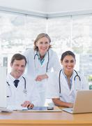 Smiling medical staff working on a laptop and a computer - stock photo