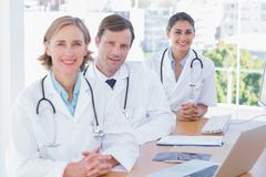 Smiling doctors posing at their desk Stock Photos