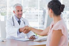 Doctor shaking hands to patient - stock photo