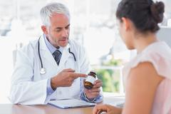 Stock Photo of Doctor explaining the bottle of pills to patient