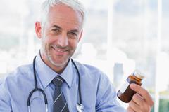 Stock Photo of Smiling doctor holding medicine jar