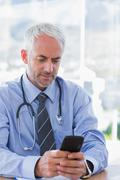 Doctor typing a text message on his smartphone - stock photo