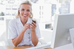 Stock Photo of Smiling nurse sitting behind a desk