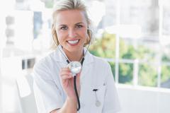 Radiant nurse showing her stethoscope - stock photo