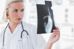 Stock Photo of Serious nurse examining a radiography