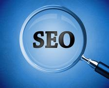 Magnifying glass revealing the word SEO Stock Photos