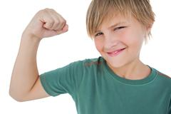 Little boy tensing arm muscle - stock photo