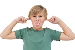 Blonde boy blocking his ears with fingers - stock photo