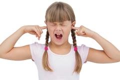 Funny little girl clogging her ears and wincing - stock photo