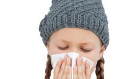 Sick little girl with an handkerchief - stock photo