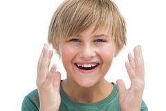 Suprised blonde boy with hands up smiling - stock photo
