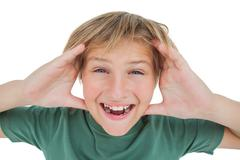 Amazed boy smiling with hands raised Stock Photos
