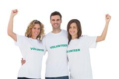 Smiling group of volunteers raising arms Stock Photos