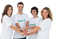 Stock Photo of Smiling volunteer group piling up their hands