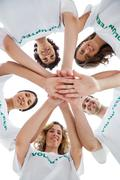 Stock Photo of Smiling group of volunteers piling up their hands