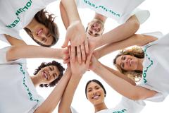 Cheerful group of volunteers putting hands together Stock Photos