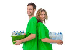 Two smiling activists holding box of recyclables and standing back to back Stock Photos