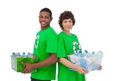 Two activists holding box of recyclables and standing back to back Stock Photos