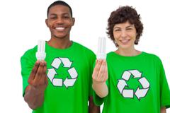 Two environmental activists holding light bulbs - stock photo
