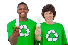 Environmental activists holding energy saving light bulbs - stock photo
