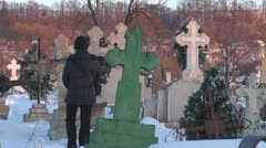 Young woman walking in cemetery in winter commemorate female snow cross sunlight Stock Footage
