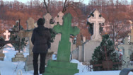 Stock Video Footage of Young woman walking in cemetery in winter commemorate female snow cross sunlight