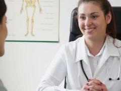 Nuori hymyilevä lääkäri puhuu hänen naispotilas toimistossa, seuranta ampui NTSC Arkistovideo