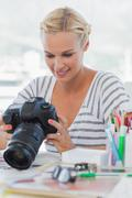 Pretty photo editor looking at her digital camera Stock Photos